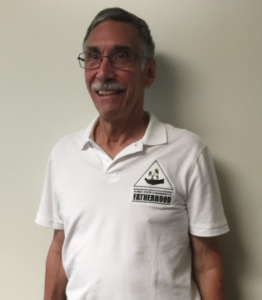 Fatherhood Commission volunteer Chet Adessa shows off the new logo featured on his polo shirt.